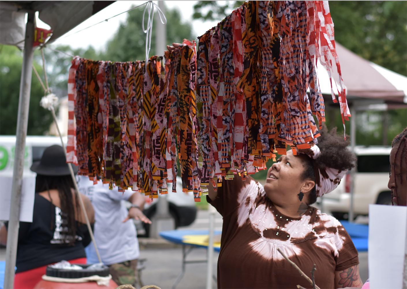 Sheba Gittens looking at colorful fabric strips at art festival