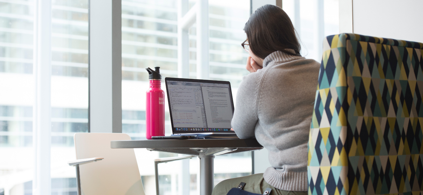 a person studying on a laptop with a pink water bottle beside