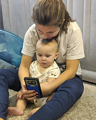 Robyn Coggins sitting with her infant son Henry looking at her phone