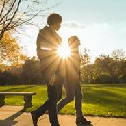 two people walking in sunlight