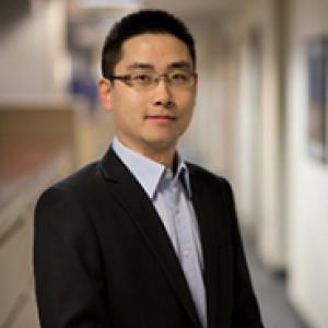Jiebiao Wang in a black jacket and dress shirt