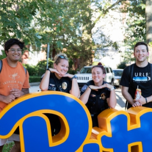 Two students and two Pitt Police Officers pose with a large script Pitt prop at an Oakland neighborhood block party