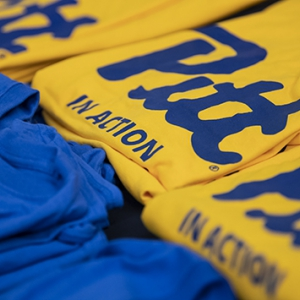 """Yellow and blue shirts that say """"Pitt In Action"""" on the front."""