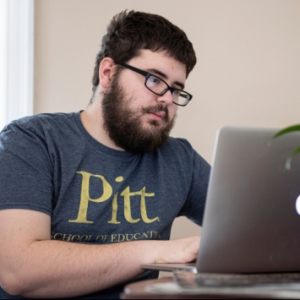 young man in a Pitt shirt working on an laptop at home