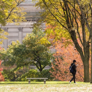 Student walking across Cathedral lawn in the fall