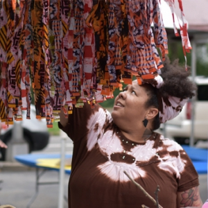 Sheba Gittens looking at colorful fabric at art festival