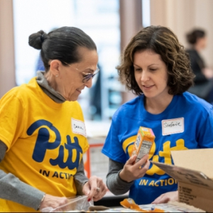Two people in Pitt shirts help pack boxes