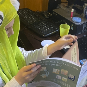 Child wearing a green alien hat reads a book to people on a Zoom virtual call