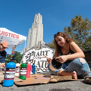 Students paint flowerpots in front of the Cathedral for PARKing Day