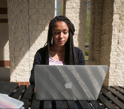 Female student working on a laptop outside