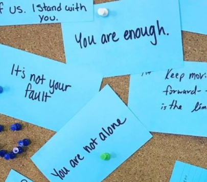 Teal cards with encouraging messages written on them posted to a cork board