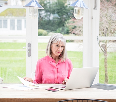 A woman in a pink shirt uses a computer in a sunroom