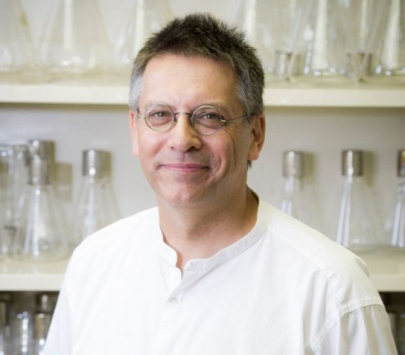 Graham Hatfull standing in front of a wall filled with flasks